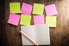 Acht leere bunte klebrige Anmerkungen und Notizbuch und Bleistift Stockfotografie