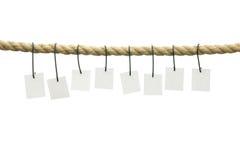 Acht leere Karten, die weg von einem Seil hängen Lizenzfreie Stockbilder