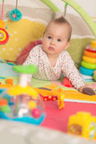 Acht maanden oud babymeisje het spelen met kleurrijk speelgoed Royalty-vrije Stock Afbeelding