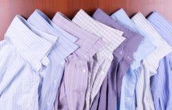 Acht mehrfarbige männliche Hemden Stockfotos