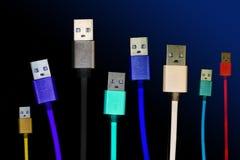 Acht mehrfarbige usb-Kabel sitzen vertikal, auf einem dunklen, düsteren lokalisierten Hintergrund Die Familie vereinigt zukünftig Lizenzfreies Stockfoto