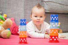 Acht Monate alte Baby, die auf den Boden legen Stockbild