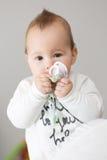 Acht Monate alte Baby, die ihren Friedensstifter zu ihrem Mund holen Lizenzfreies Stockfoto