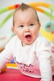 Acht Monate alte Baby, die mit bunten Spielwaren spielen Stockfoto