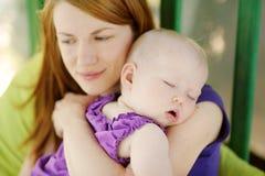 Acht Monate alte Schätzchen, die in den Mutterhänden schlafen Lizenzfreie Stockbilder