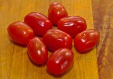 Acht rote Minikirschtomaten Lizenzfreies Stockbild
