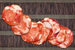 Acht Schweinefleisch-Salami-Scheiben eingestellt auf Weinlese-rustikalen verschachtelten Pergament-Platz Mat Rough Grunge Surface Stockfoto