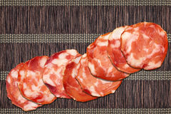 Acht Schweinefleisch-Salami-Scheiben eingestellt auf Weinlese-rustikalen verschachtelten Pergament-Platz Mat Rough Grunge Surface Lizenzfreie Stockfotografie