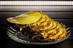 Acht stukken van rijpe ananas liggen in een transparante plaat op een donkere houten achtergrond royalty-vrije stock afbeeldingen