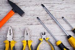Acht Werkzeuge liegen an der Unterseite auf einem grauen hölzernen Hintergrund Ansicht von oben Lizenzfreie Stockbilder