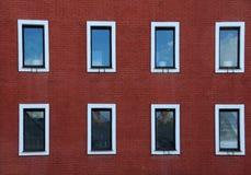 Acht Windows auf Wand des roten Backsteins Stockbilder