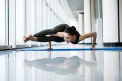 Acht-Winkel-Haltung Frauenyogapraxishaltungs-Trainingskonzept in der Turnhallenhalle mit großen Fenstern Stockfoto