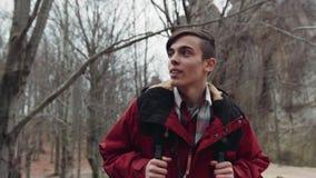 Achteloze jonge aantrekkelijke toerist die in het de herfstbos wandelen met een rugzak Groot avontuur Mannelijk portret stock video