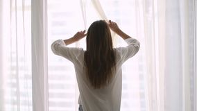 Achter achtermening bij rijk gelukkig jong vrouw het openen gordijn stock footage
