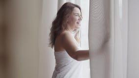 Achter achtermening bij rijk rijp vrouw het openen gordijnkant die zich in het huis van de luxeflat bevinden of het moderne hotel stock footage