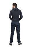 Achter achtermening van de gebaarde mens in zwart sweatshirt die met een kap weg eruit zien Stock Fotografie