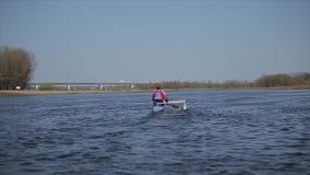 Achter brede mening van Atleet het roeien op de rivier in een kano Het roeien, canoeing, het paddelen Opleiding kayaking E stock video