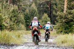 achter de atletenvulklei van twee motocrossenduro van vuil en water Stock Foto