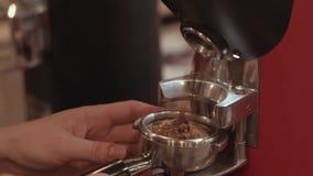 Achter de koffiebar giet de koffiemolen grondkoffie in houder, weg neemt de vrouwelijke baristashand het Baristasportret stock videobeelden