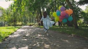 Achter kijk van het jonge meisje lopen in het groene park en houdt kleurrijke ballons stock videobeelden