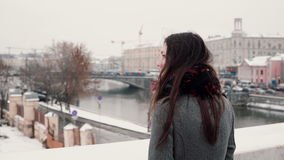 Achter mening De aantrekkelijke jonge donkerbruine meisje status op de brug en bekijkt de snow-covered de winterstad Stock Fotografie