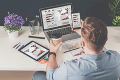 Achter mening De jonge gebaarde zakenman in denimoverhemd zit in bureau bij lijst en gebruikt smartphone met grafieken, diagramme stock afbeeldingen