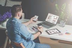 Achter mening De jonge gebaarde zakenman in overhemd zit in bureau bij lijst en gebruikt smartphone met grafieken, diagrammen en  royalty-vrije stock foto's