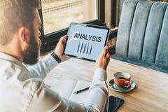Achter mening De jonge gebaarde zakenman in wit overhemd zit bij lijst, gebruikend tabletcomputer met grafieken en grafieken royalty-vrije stock afbeeldingen