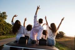 Achter mening De jonge kerels zitten en houden handen in zwarte cabriolet op de landweg op een zonnige dag omhoog stock foto