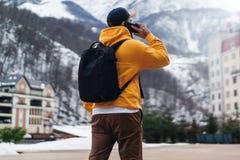 Achter mening De mensentoerist in gele hoodie met zwarte rugzak bevindt zich op achtergrond van hoge sneeuwbergen, die op mobiele royalty-vrije stock fotografie
