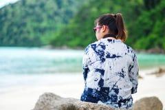 Achter mening de vrouw die van Azië zonnebril en sittin van het indigooverhemd dragen Royalty-vrije Stock Foto's