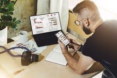 Achter mening Freelancer zit huis bij lijst, werkt aan laptop computer met grafieken, grafieken, diagrammen op monitor, gebruiken stock afbeelding