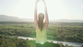 Achter mening Jonge sportieve vrouw het praktizeren yoga op de bovenkant van berg bij zonsondergang Slanke vrouw die gymnastiek o stock footage
