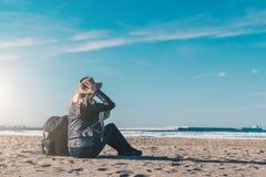 Achter mening Jonge vrouwentoerist in hoed en met rugzakzitting op strand en het kijken op zee, op kustlijn, op horizon royalty-vrije stock fotografie