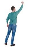 Achter mening van de mens Hief omhoog zijn vuist in overwinningsteken op Achtergedeelte vi Royalty-vrije Stock Afbeelding