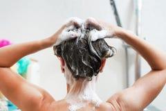 Achter mening van jonge vrouw die haar haar wast stock afbeeldingen