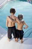 Achter mening van jongens die in zwembad kijken royalty-vrije stock foto