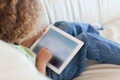 Achter menings jonge jongen die een tabletcomputer met behulp van Stock Foto's