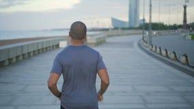 A achter meningsportret van de Afrikaanse Amerikaanse jonge en geschikte atletenmens die en in de stadsstraat opleiden lopen stock videobeelden