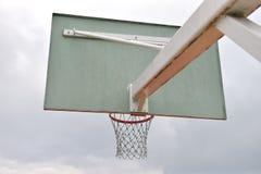 Achter van basketbalraad onder bewolkte hemel in een schoolwerf Co Royalty-vrije Stock Afbeeldingen
