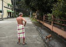 Achter van de oude mens met lendendoek die zich met zijn huisdier op openbare straat bevinden Royalty-vrije Stock Foto