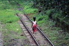 Achter van Myanmarese-damedorpsbewoner die op de spoorwegsporen lopen en gezet de bezittingen op het hoofd stock foto's