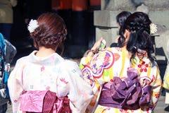 Achter van vrouwen in Kimonokleding en donkerroze sjerp in Japanse tempel royalty-vrije stock afbeeldingen