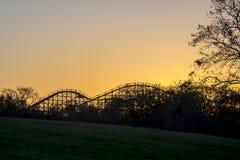 Achterbahn über einem Hügel mit einem brennenden Sonnenuntergang Stockbild