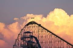 Achterbahn am angemessenen Freizeitpark des Tales silhouettiert gegen DRA Lizenzfreie Stockbilder