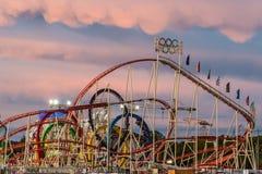 Achterbahn in Oktoberfest während des Sonnenuntergangs Lizenzfreie Stockfotos