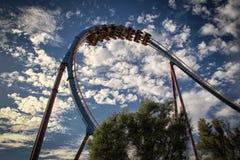 Achterbahnschleife mit einem Hintergrund des schönen bewölkten Himmels Lizenzfreies Stockbild
