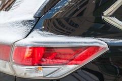 Achterdieeindelichten van auto met sneeuw worden behandeld royalty-vrije stock afbeeldingen