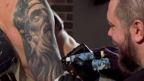 Achterdiemening van een tattoist wordt geschoten die tatoegeringen op het wapen van mannelijke cliënt maken stock video