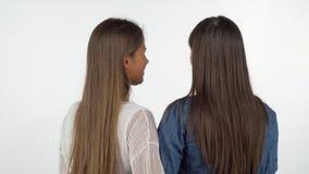Achterdiemening van twee vrouwelijke vrienden wordt geschoten die aan de camera over hun schouders glimlachen stock videobeelden